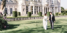newly wed couple walking in the gardens of ashridge house