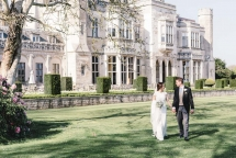 newly wed couple walking hand in hand in the gardens of ashridge house